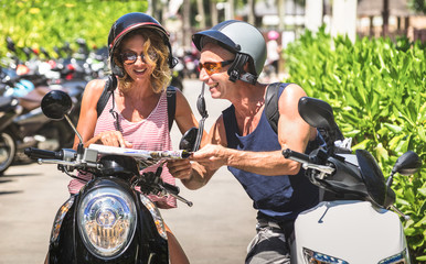 Happy couple of tourist travelers around Patong with motorbike scooter - Wander friends having fun on road trip in Phuket island Thailand - Travel concept with adult people on world tour - Warm filter