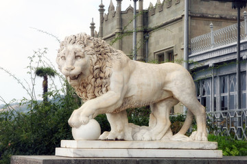 big old beautiful white marble statuary of lion with ball in Crimea