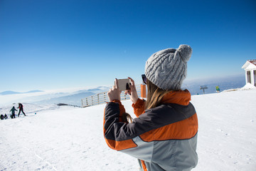 Taking picture of the ski lane where she is going to ski