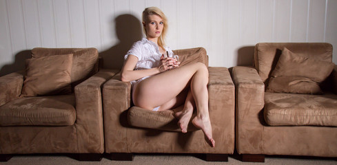 shaved-hair girl is sitting in the armchair and drinking hot tea