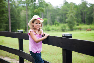 Little Girl on a Fence at a Horse Farm and Ranch