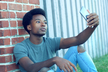 young man taking selfie outside sitting in grass wearing jeans smartphone pic portrait technology