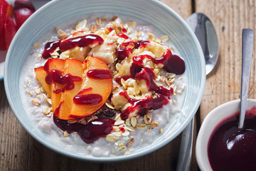 Strawberry porridge with oats, mashed banana and plum and blueberry sauce