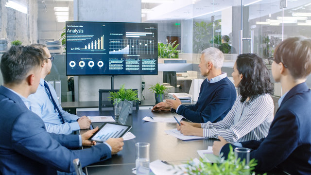 Diverse Group of Successful Business People in the Conference Room, Discuss  Company's Growth Shown on the Wall TV Illustrated by Charts and Statistics.