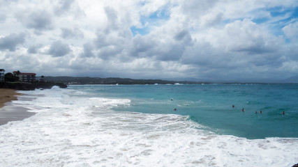 Many people swimming in the waves during a cloudy but beautiful day at a Dominican beach in Sosùa.