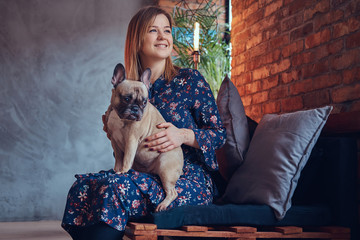 Portrait of a smiling attractive woman sitting with a cute pug i