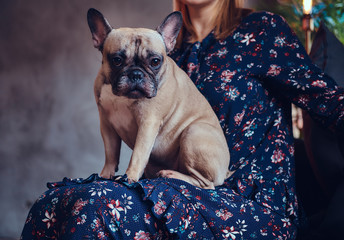 Portrait of a woman sitting with a cute pug in a room with loft