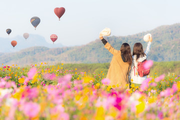 Tourist asian woman relax and freedom in beautiful blooming cosmos flower garden and see hot air balloon in a field.  Travel and Lifestyle Concept.