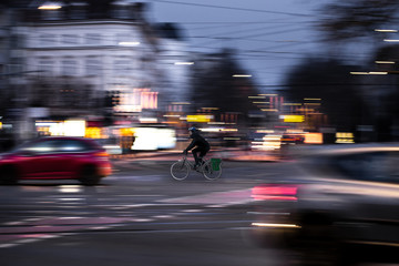 A cyclist drives at twilight over a road intersection Fototapete