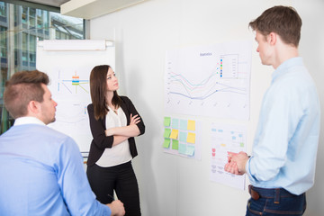 Business People Discussing Over Line Graph In Office