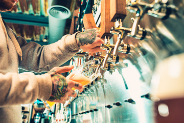 Hand of bartender pouring a large lager beer in tap.