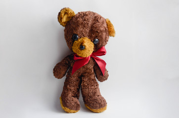 Old brown teddy bear with a pink ribbon