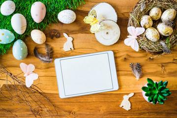 Freifläche auf Tablet auf Holztisch im Hintergrund und bunte verzierte Ostereier, Federn, Schmetterlinge von oben zu Ostern