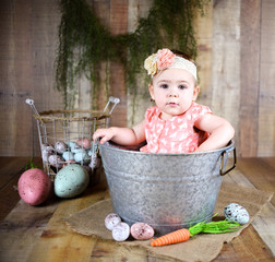 Cute adorable Caucasian baby girl wearing a bow and sitting in a bucket with Easter eggs around for a vintage look