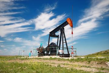 Oil pump. Oil industry equipment in green meadow