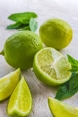 Fresh juicy lime, wedges and mint close-up on a light wooden table