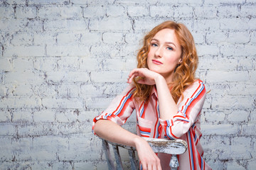 portrait Beautiful young woman student with red curly hair and freckles on her face sitting on a wooden chair on a brick wall background in gray. Dressed in a red striped shirt.