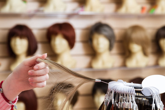 girl in her hand chooses a hair color wig of a natural blond. A palette of hues of hair color in a store of wigs on a blurry