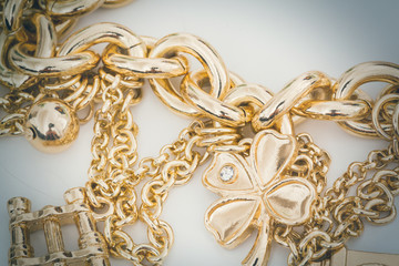 Close up of a lucky gold shamrock or four leafed clover charm with small diamond on a bracelet