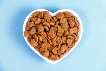 Dry cat food in the form of hearts lies in the saucer in the form of heart