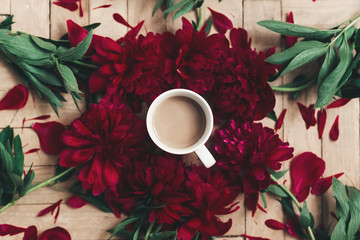 stylish coffee and beautiful red peonies on rustic wooden background flat lay. space for text. modern floral instagram blogging image. happy womens day or mothers