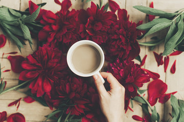 hand holding stylish coffee and beautiful red peonies on rustic wooden background flat lay. space for text. modern floral instagram blogging image. happy womens day or mothers