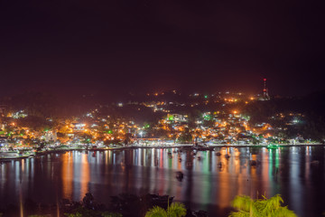 Samana, Dominican Republic. View on the village in the night. Colorful lights among the palm trees and houses. Samana Bay and reflection of the village on the water.