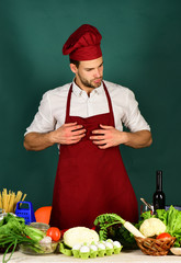 Cook works in kitchen near table with vegetables and tools.