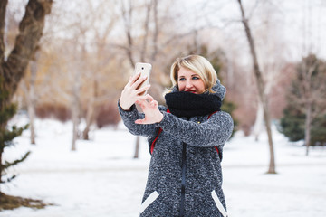 Young beautiful hipster girl is looking into the camera phone and smiling outdoors in winter. A girl makes selfie for a walk in the winter.