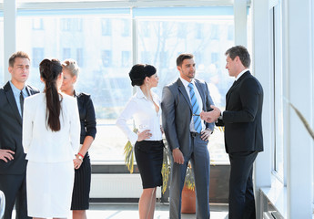 group of business people talking,standing in the lobby of the office.
