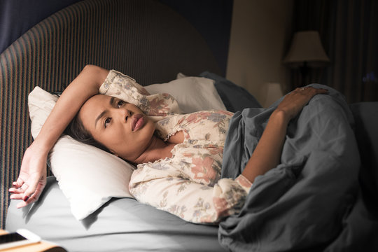 Sadly depressed women suffer from insomnia, she sleep in bed and touching her forehead, sleep disorder and stress concept.