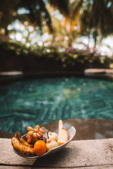 Close-up of fruits in a bowl beside the pool