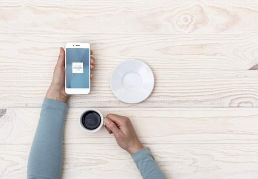 Smarphone User at Bright Wooden Table with Coffee Mockup 1