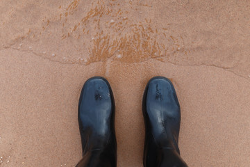 Black rubber boots on the sand top view. Feet in rubber boots in water