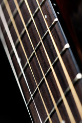 A guitar fretboard with strings on black background