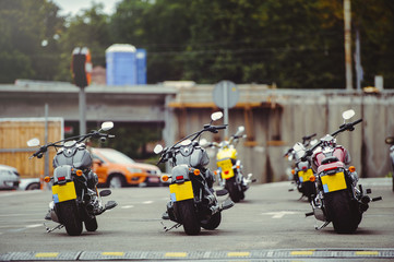 motorcycles stand in the parking lot in anticipation of riders, motorcycle rear view, moto travel