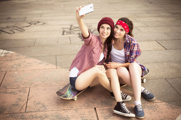 Two Brunette teenage girls friends in hipster outfit (jeans shorts, keds, plaid shirt, hat) with a skateboard at the park outdoors make selfie on a phone. Copy space