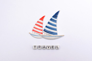 Two yachts with blue and red sails on a white background with an inscription travel