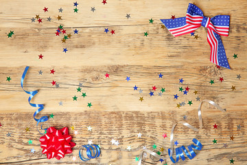 American flag bow and confetti on wooden background. USA holiday