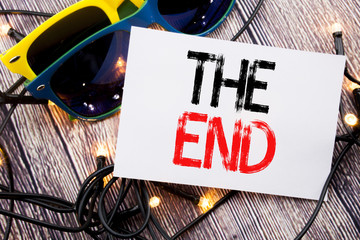 Writing text showing The End. Business concept for End Finish Close written on sticky note with copy space on old wood wooden background with sunglasses
