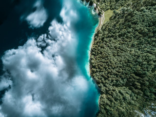 Aerial Reflection of blue partly cloudy sky in a calm lake with forest to the right