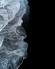 Minimalist and abstract Aerial view of waves breaking on black sand beach