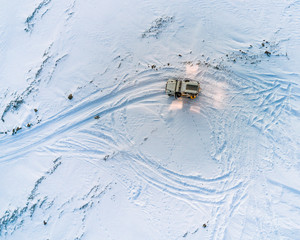 Aerial of a 4 by 4 vehicle with tracks in the snow on top of a glacier in iceland during dusk