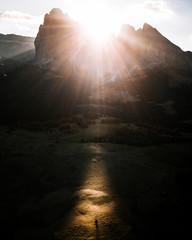 Sunrise over Dolomites Alpe di Siusi with single tree right where the sunbeam hits