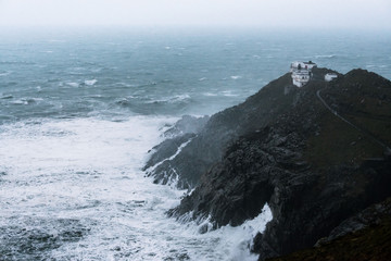 Cliffs at Mizen Head signal station on the south Ireland coast during heavy storm and crashing waves Wall mural