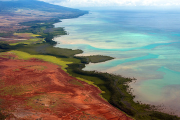 Aerial view of the colorful coast and Pacific water of the island of Molokai, Hawaii, shot from a small, low-flying prop plane