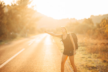 Young backpacking adventurous woman hitchhiking on the road.Stopping a car with a thumb.Travel lifestyle.Low budget traveling.Adventurous active vacations.Hitchhiking tourism concept.Backpacker
