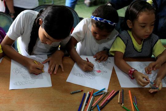 Children color a graphic design in the shape of Venezuela in the slum of Petare in Caracas