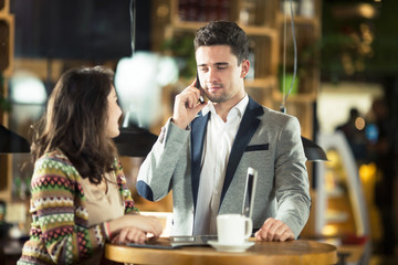 Two young businessman having a  meeting at cafe
