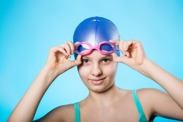 Portrait of a girl sportswoman in a bathing cap and glasses. The girl wears diving goggles. A bright blue background.